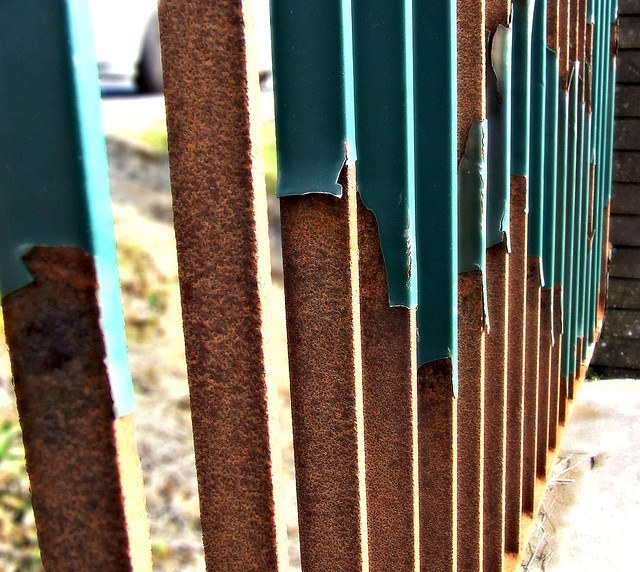 worn rusted steel fence